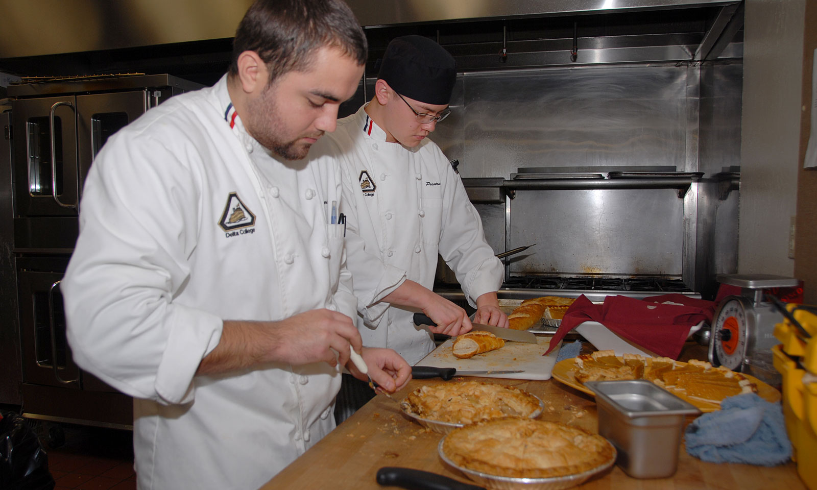 Students cut a pie during Culinary Arts Lab class.