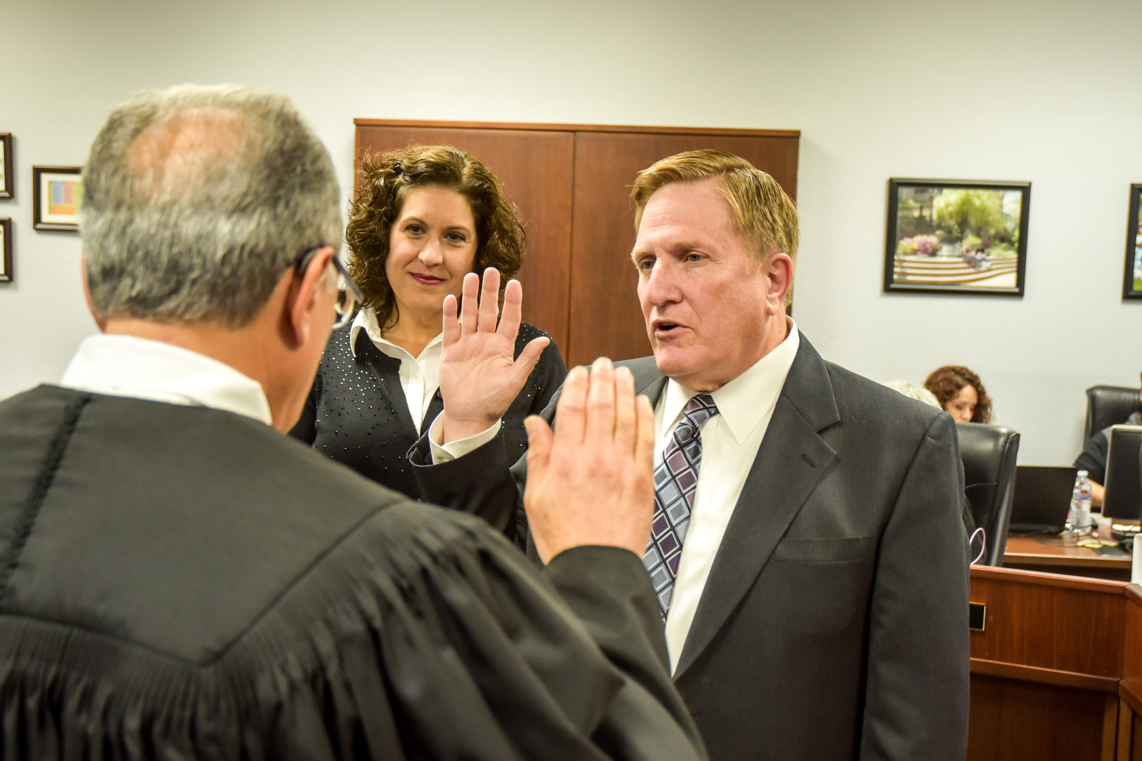 New San Joaquin Delta College Trustee Charles Jennings is sworn in while his wife, Heather, watches.