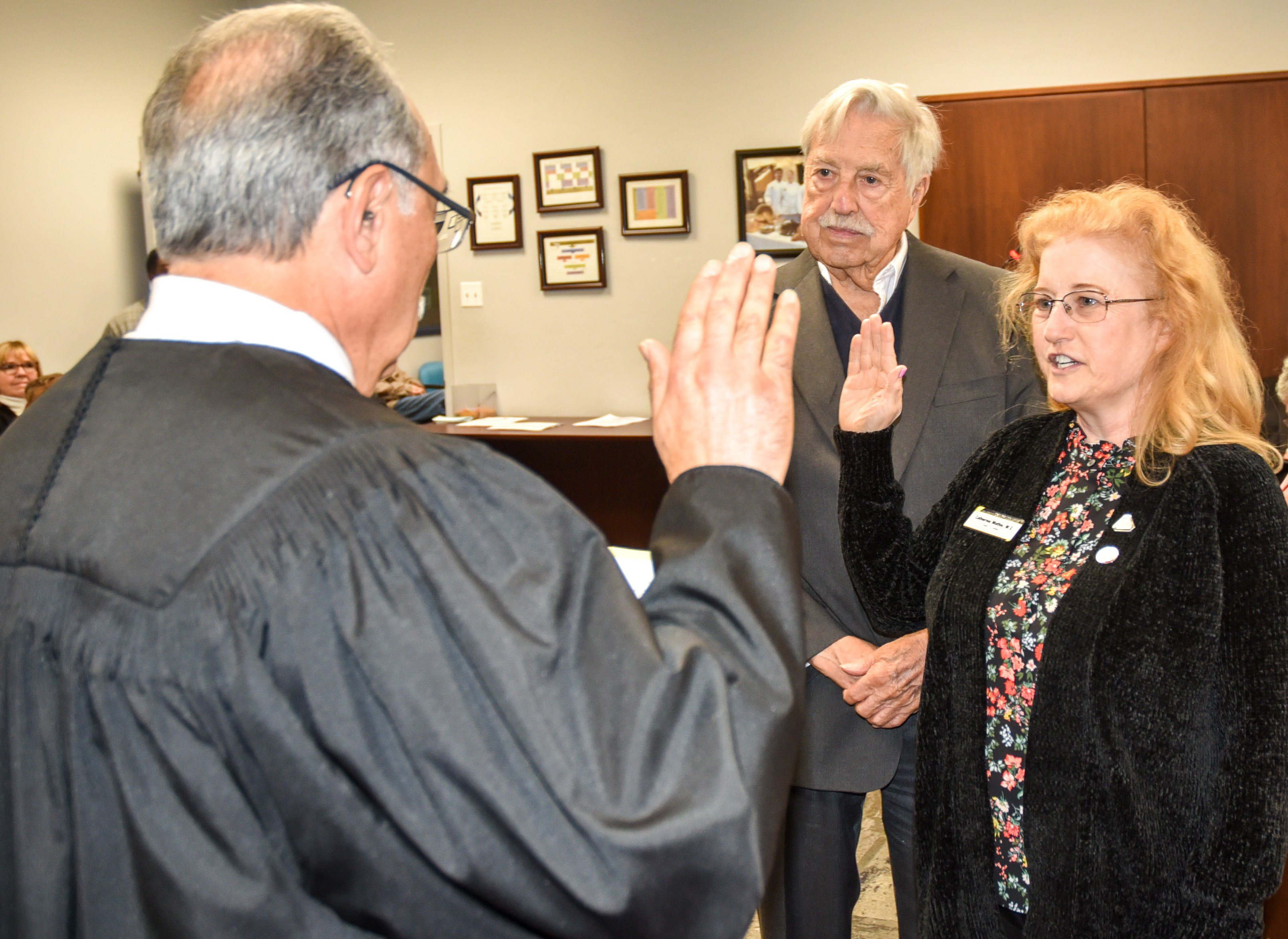 Returning San Joaquin Delta College Trustee Catherine Mathis is sworn in while her husband, Millard Frohock, watches.