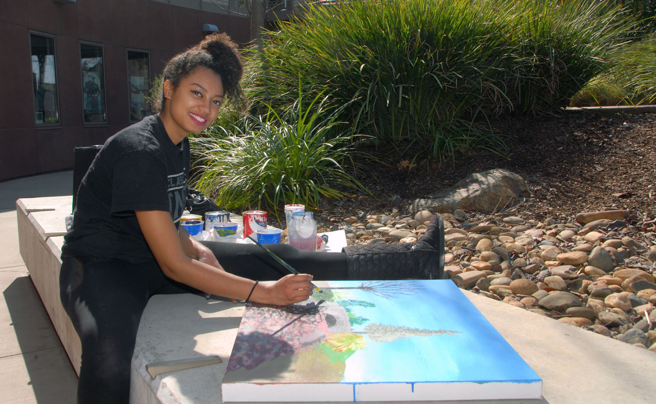 Student artist paints outside at Delta College