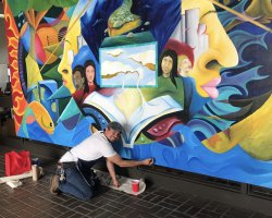 San Joaquin Delta College Professor Mario Moreno touches up a mural that was recently reinstalled on the Stockton campus.