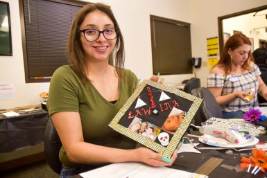 Graciela Villa enrolled at San Joaquin Delta College following the birth of her son, Adan. She was one of more than a dozen students through the CalWORKs program who decorated their commencement caps as a group this week.