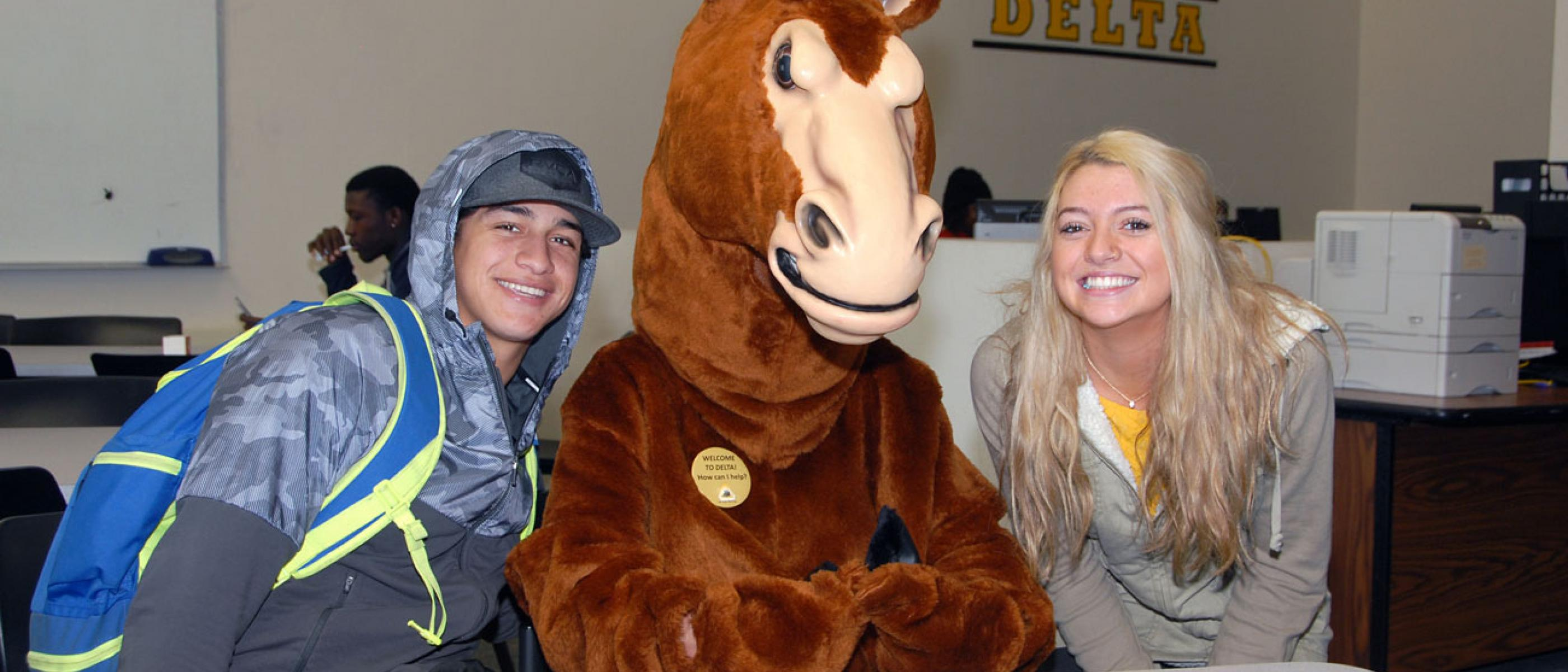 Students pose with the Delta mascot at the Zone