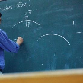 Teach performs physics equation on chalkboard