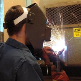 Student operates tools in welding class